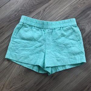 Green J crew shorts.